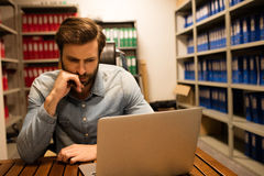 使用膝上型计算机的体贴的商业主管在文件存储室 免版税库存照片