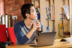 使用膝上型计算机的体贴的年轻亚裔人在咖啡馆 免版税库存照片