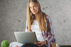 使用膝上型计算机的俏丽的夫人在工作场所 免版税库存照片