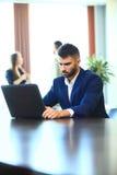 使用膝上型计算机的偶然女实业家在办公室 免版税库存图片