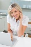 使用膝上型计算机的偶然妇女,当在电话在厨房时 免版税库存照片