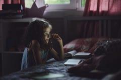 使用膝上型计算机的儿童女孩和观看电影在单独晚上在她的屋子里 图库摄影