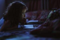 使用膝上型计算机的儿童女孩和观看电影在单独晚上在她的屋子里 免版税库存图片