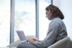 使用膝上型计算机的公执行委员在等候室 库存照片