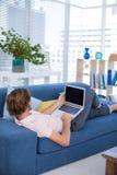 使用膝上型计算机的公执行委员,当放松在沙发时 免版税库存图片