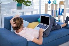使用膝上型计算机的公执行委员,当放松在沙发时 库存照片