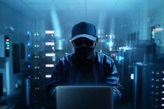 使用膝上型计算机的匿名黑客在服务器屋子里 免版税图库摄影