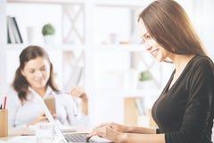 使用膝上型计算机的华美的女孩在工作场所 库存图片