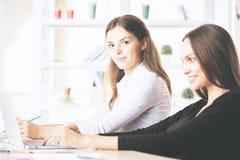 使用膝上型计算机的华美的妇女在工作场所 免版税库存图片