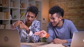 使用膝上型计算机的印度和非裔美国人的男生特写镜头射击和谈论愉快地微笑的开会 影视素材