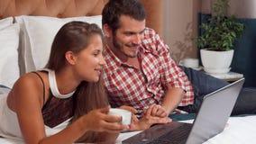 使用膝上型计算机的可爱的夫妇在他们的酒店房间,当食用咖啡时 股票视频