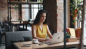 使用膝上型计算机的可爱的女孩在单独咖啡馆的咖啡馆键入的微笑的工作 股票录像