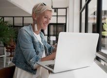 使用膝上型计算机的可爱的妇女在咖啡店 免版税图库摄影