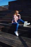 使用膝上型计算机的可爱的少妇坐享受晴天的木楼梯户外 库存图片