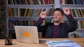 使用膝上型计算机的可爱的愉快的商人握他的在头后的手和放松开会在图书馆 影视素材
