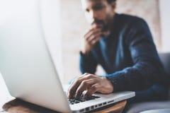 使用膝上型计算机的可爱的有胡子的非洲人,当坐沙发在他的现代家庭办公室时 青年人的概念 免版税图库摄影