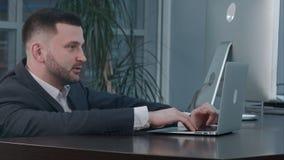 使用膝上型计算机的可爱的白种人商人,当谈话与伙伴在工作场所时 免版税库存图片
