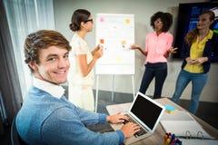 使用膝上型计算机的同事微笑对照相机,当工友谈论在whiteboard时的流程图 库存图片
