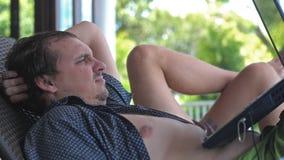 使用膝上型计算机的哀伤的人在阳台在手段在度假 图库摄影