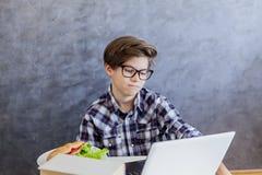 使用膝上型计算机的哀伤的青少年的男孩和食用早餐 库存照片