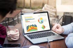 使用膝上型计算机的商人分析在膝上型计算机屏幕上的统计数据,与图表一起使用在网上绘制在会议上 免版税库存图片