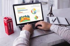 使用膝上型计算机的商人分析在膝上型计算机屏幕上的统计数据,在网上与图表图一起使用 库存照片