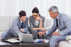 使用膝上型计算机的商人和在沙发 免版税库存照片