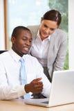 使用膝上型计算机的商人和女实业家在办公室 免版税图库摄影