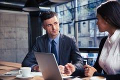 使用膝上型计算机的商人和女实业家在咖啡馆 库存照片
