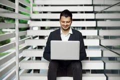 使用膝上型计算机的商人在台阶 在经典成套装备的微笑的男性,当浏览互联网时 库存照片