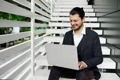 使用膝上型计算机的商人在台阶 在经典成套装备的微笑的男性,当浏览互联网时 库存图片