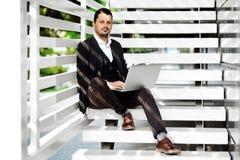 使用膝上型计算机的商人在台阶 免版税库存照片