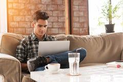 使用膝上型计算机的商人在咖啡店的沙发 库存图片
