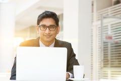 使用膝上型计算机的商人在咖啡馆 库存照片