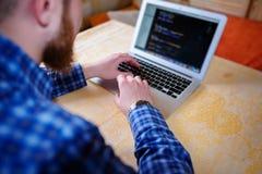 使用膝上型计算机的商人在工作场所-背面图 免版税库存图片