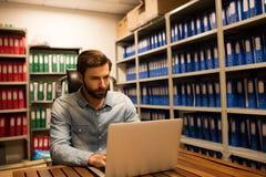 使用膝上型计算机的商人在文件存储室 库存照片