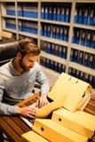 使用膝上型计算机的商人在桌上在文件存储室 图库摄影