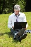 使用膝上型计算机的商人在草甸 库存照片