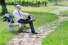 使用膝上型计算机的商人坐长凳 免版税图库摄影