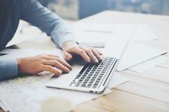 使用膝上型计算机的商人新的建筑项目的 在桌上的普通设计笔记本 被弄脏的背景 图库摄影