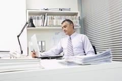 使用膝上型计算机的商人有在书桌的文书工作的 库存图片