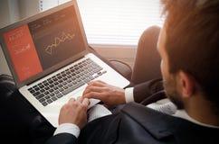使用膝上型计算机的商人有在屏幕上的银行帐户的 免版税库存照片