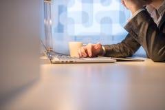 使用膝上型计算机的商人用在边的咖啡 库存图片
