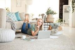 使用膝上型计算机的喜悦的年轻女人在客厅 免版税库存照片