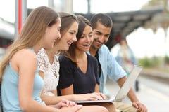 使用膝上型计算机的四个朋友在火车站 免版税库存照片