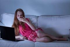 使用膝上型计算机的困女孩在晚上 免版税图库摄影
