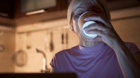 使用膝上型计算机的困资深女实业家在家庭办公室 从纸杯的疲乏的女性饮用的咖啡 股票视频