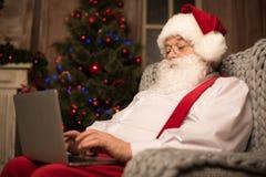 使用膝上型计算机的圣诞老人 库存照片