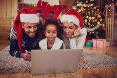 使用膝上型计算机的圣诞节非洲的非洲年轻快乐的家庭 免版税库存图片