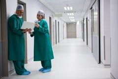使用膝上型计算机的外科医生在走廊 免版税库存图片